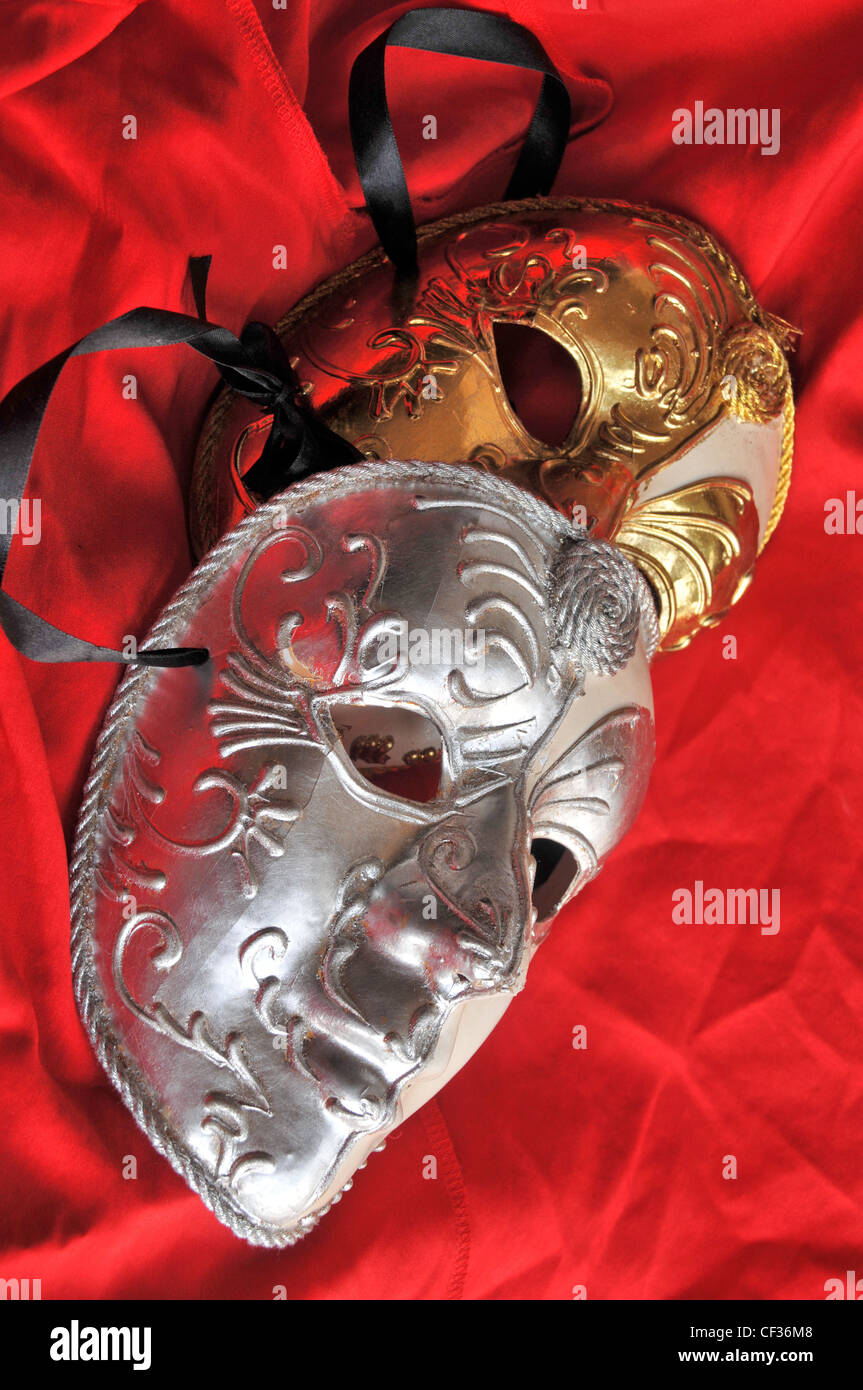 Two theatrical  silver and gold coloured face masks against red satin material. - Stock Image