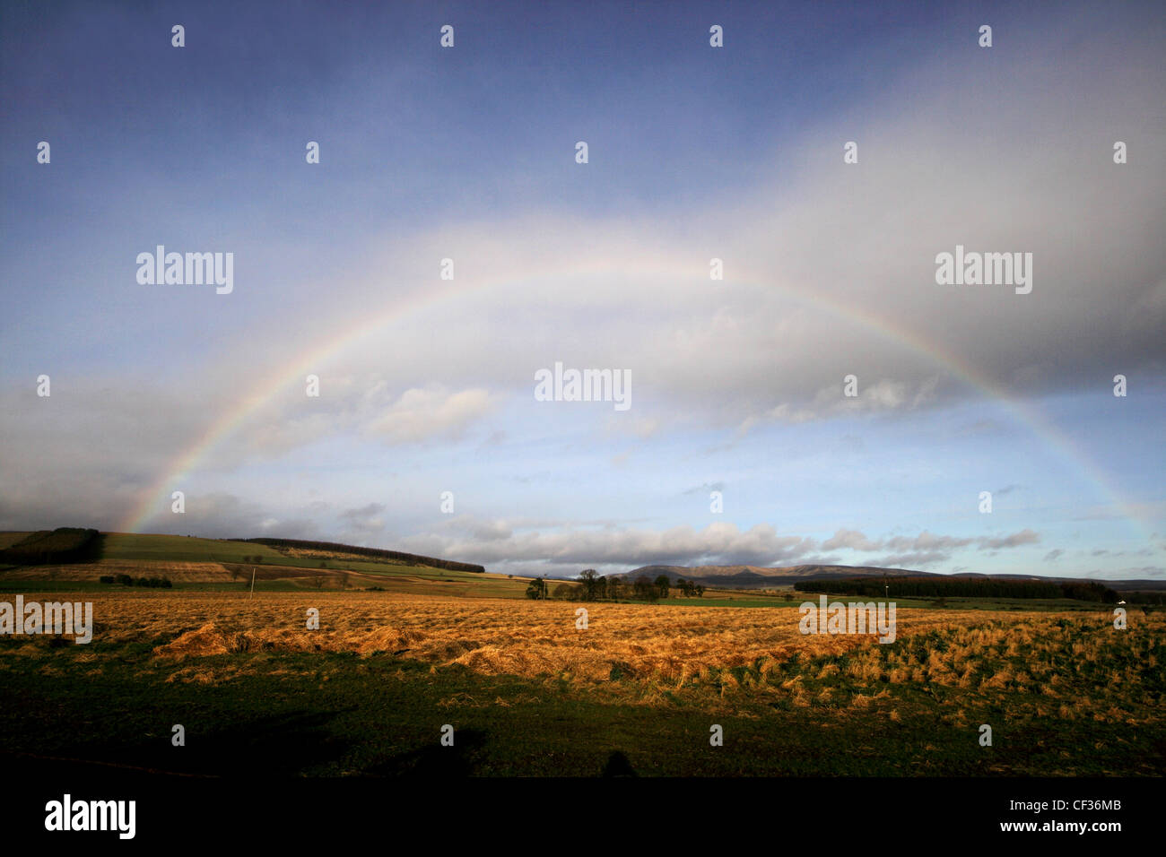 A rainbow viewed over Aberdeenshire hills and farmland. The area consists of fertile farmlands of the Mearns and - Stock Image