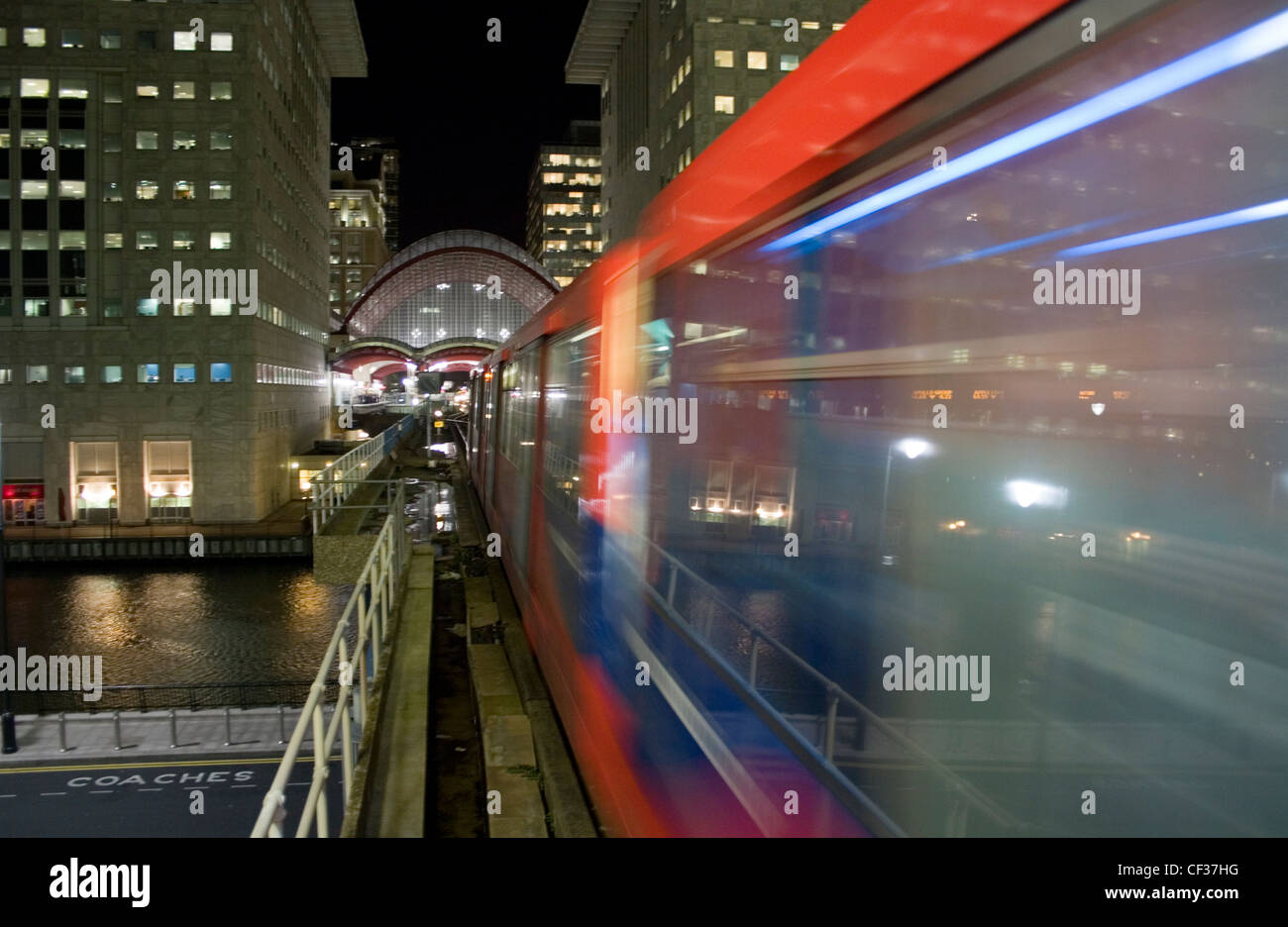 Docklands Light Railway train approaching towards Canary Wharf station at night. - Stock Image