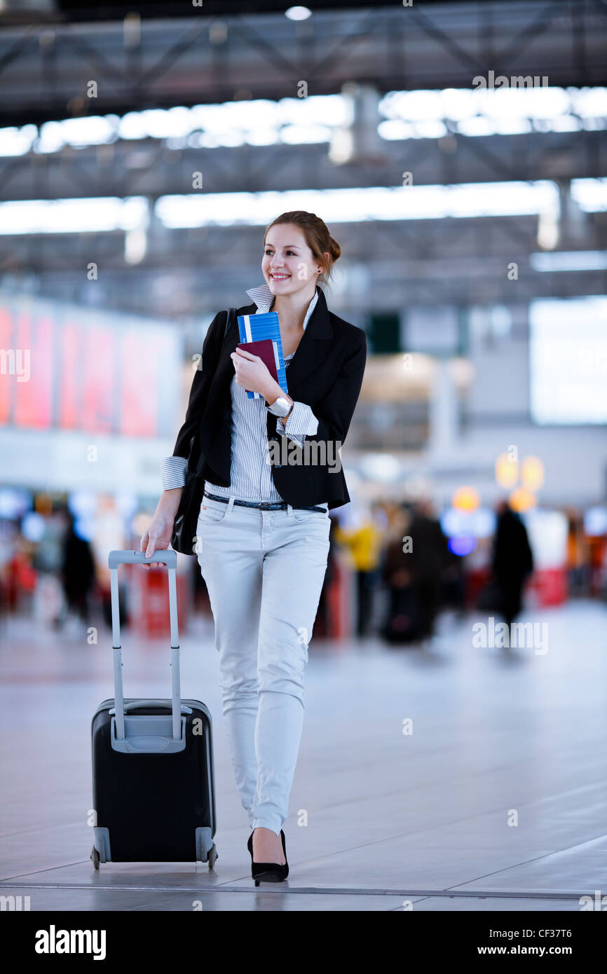 Pretty young female passenger at the airport - Stock Image
