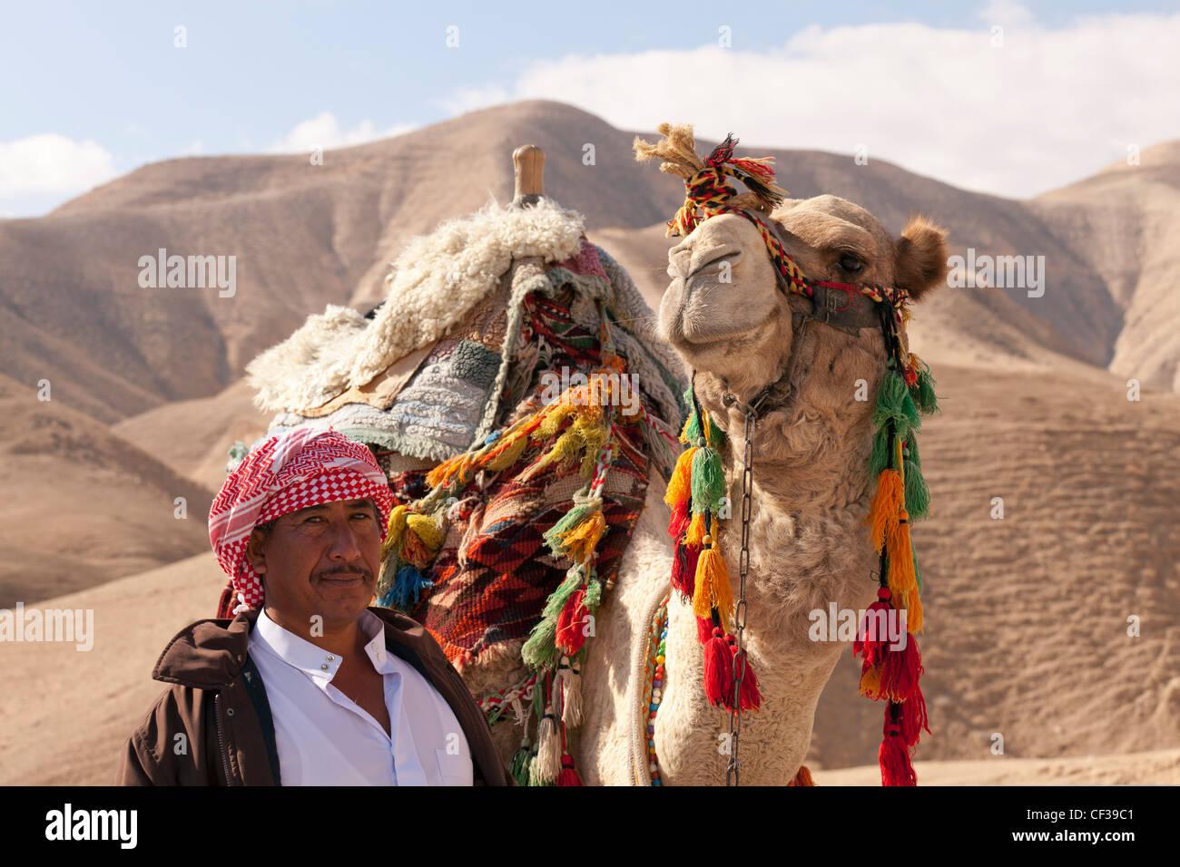 Israel, Judean Desert,Bedouin and camel in desert setting Stock Photo