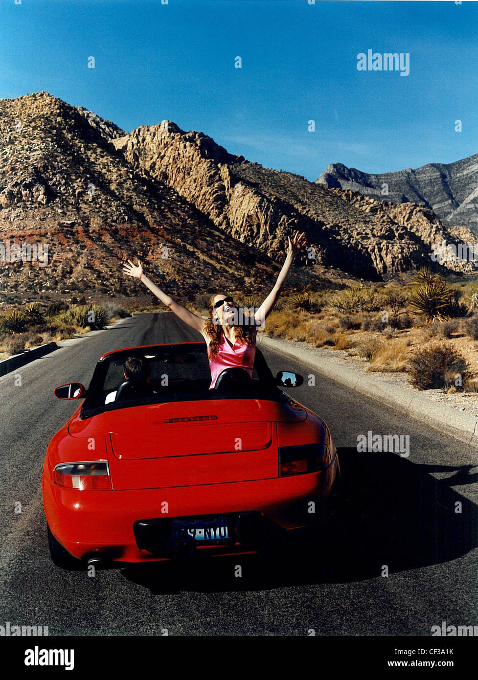 Couple in red soft top Porsche car, female with arms in air  Frowein - Stock Image