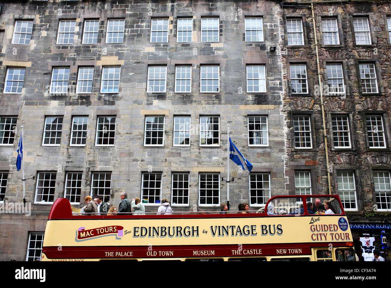 Tourists aboard an open top bus on The Royal Mile in the Old Town of Edinburgh. - Stock Image