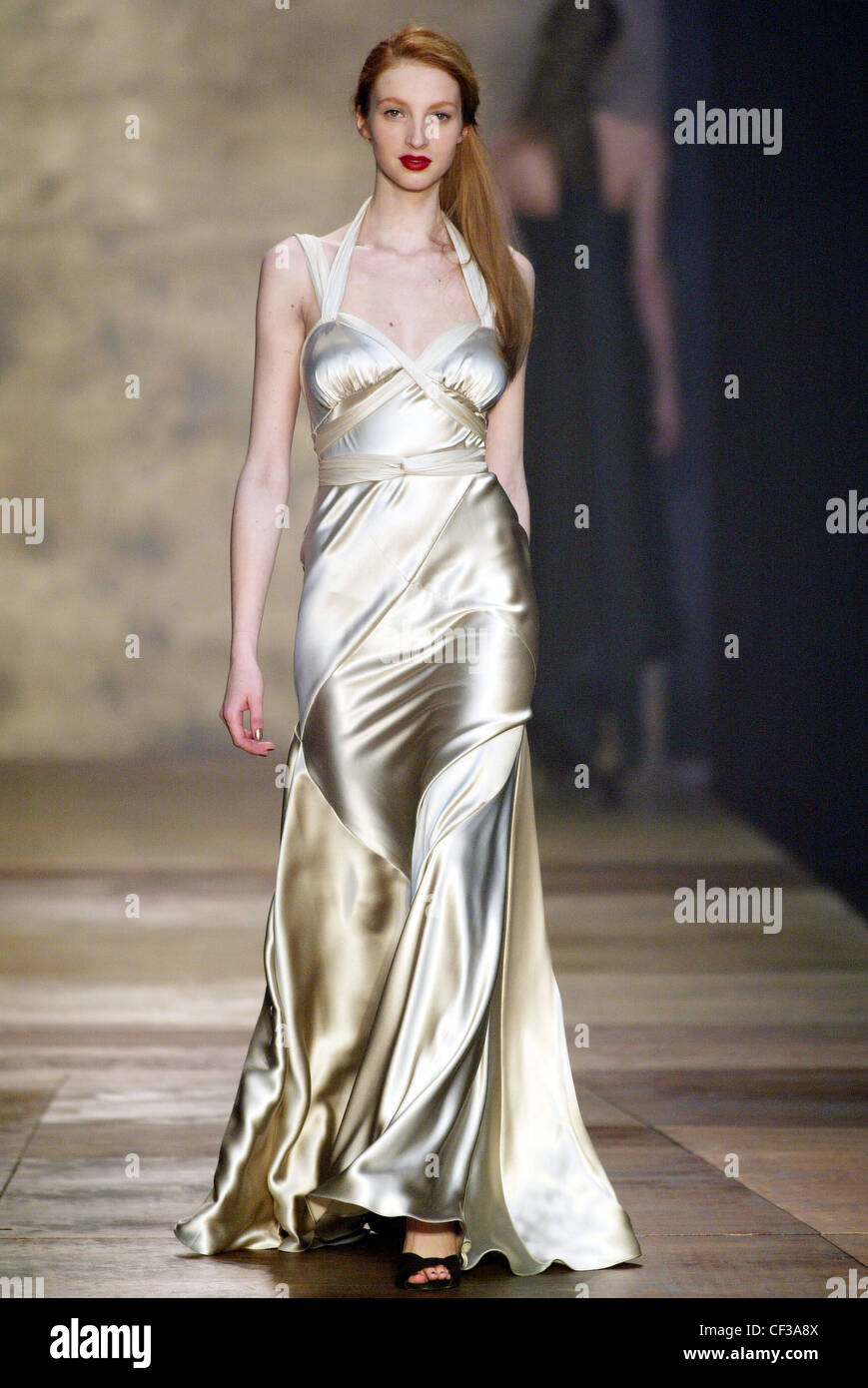 Female model red hair wearing a maxi length silvery evening gown ...