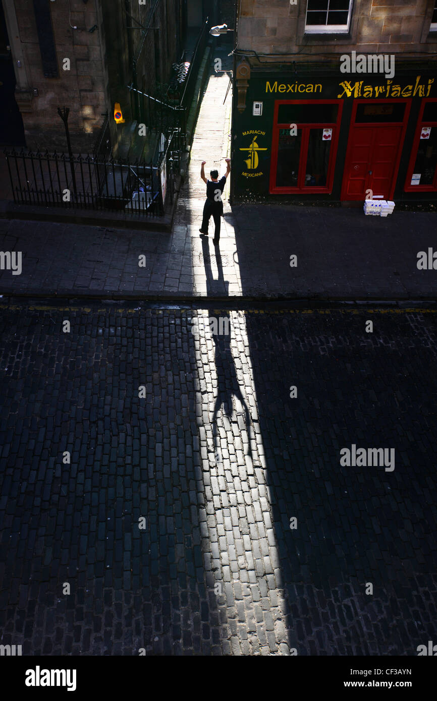 A man silhouetted in Victoria Sreet in the Old Town of Edinburgh. - Stock Image