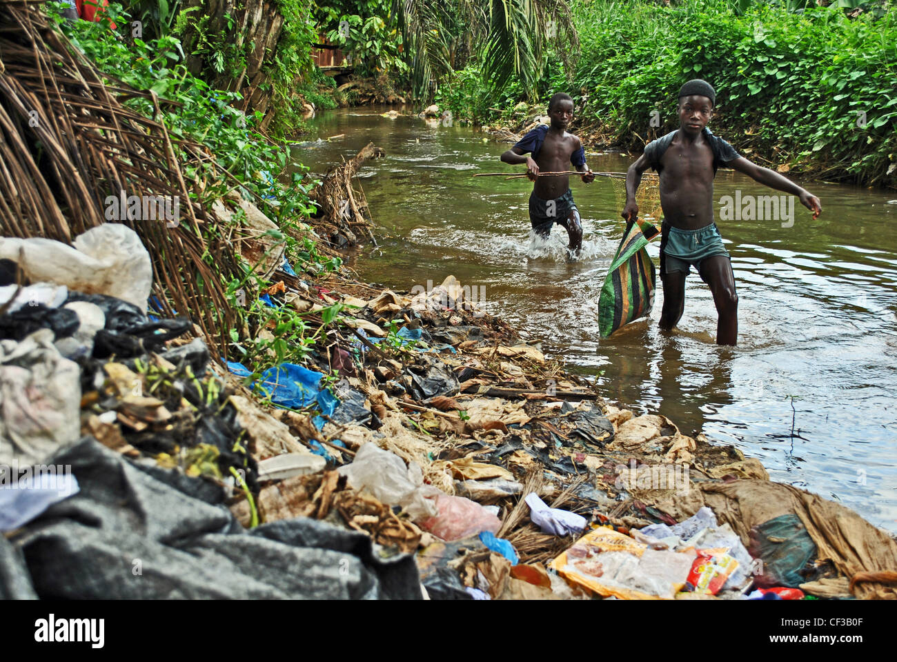 Boys fishing in a polluted stream outside Kenema, Sierra Leone - Stock Image