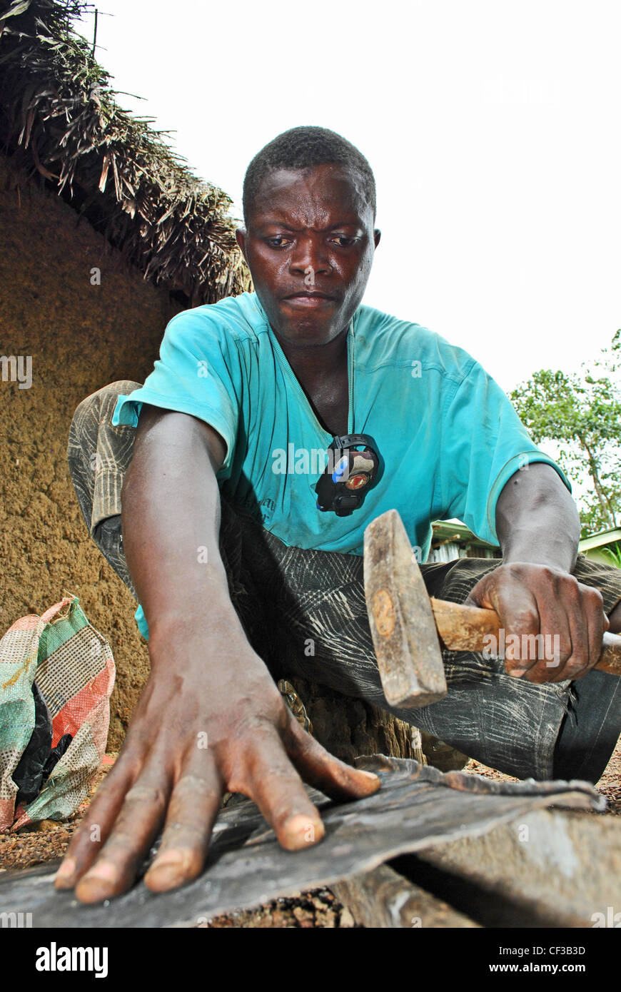 A tinsmith works with a hammer at his workshop in Bo, Sierra Leone Stock Photo