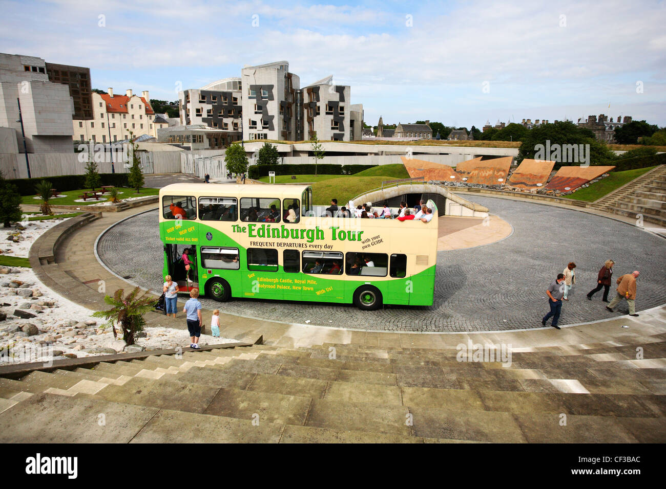 View over the Scottish Parliament and bus dropping off people at the Dynamic Earth Centre. - Stock Image
