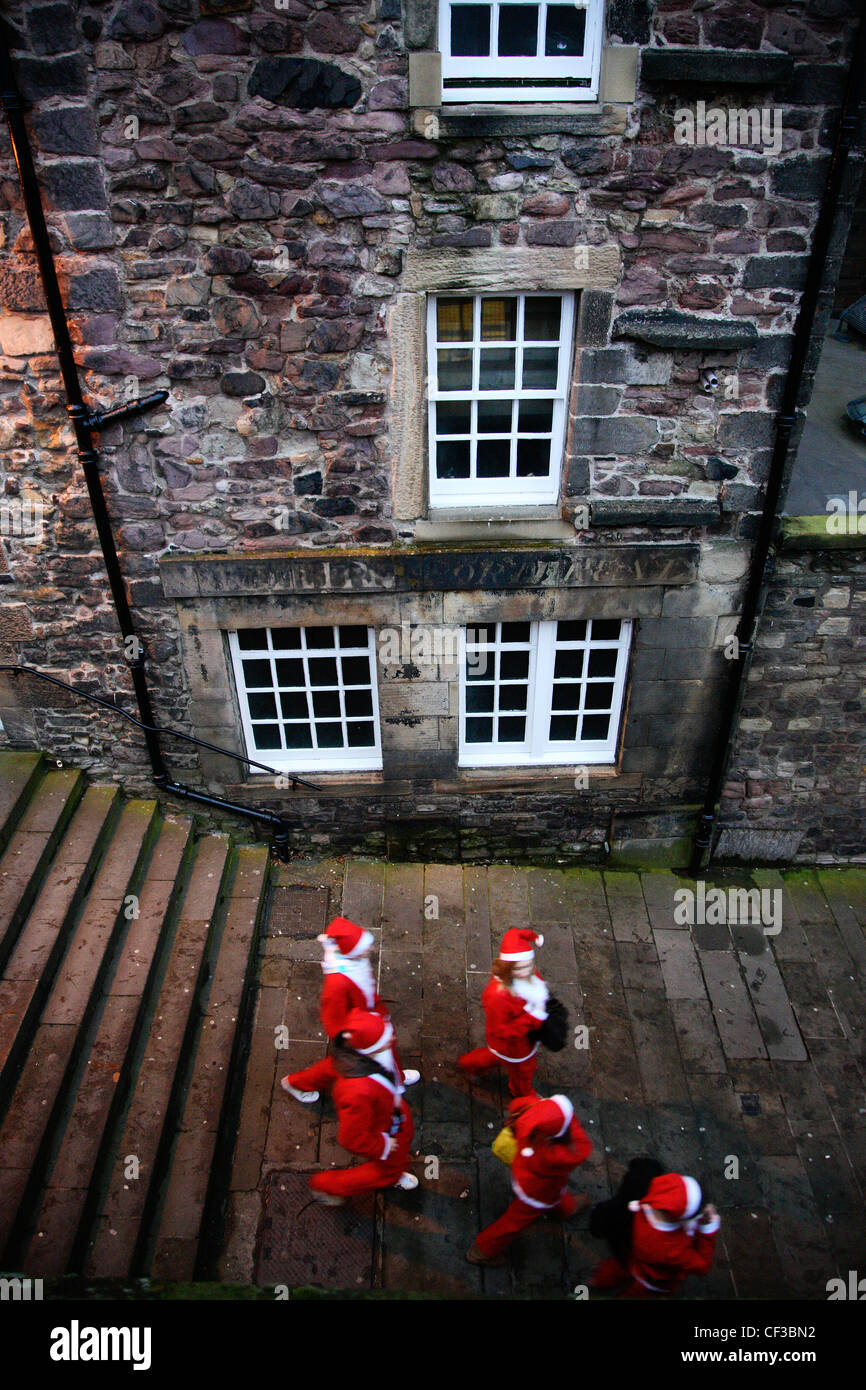 Looking down on the streets to a group of people in costume during the Edinburgh Christmas Santa Stroll. - Stock Image