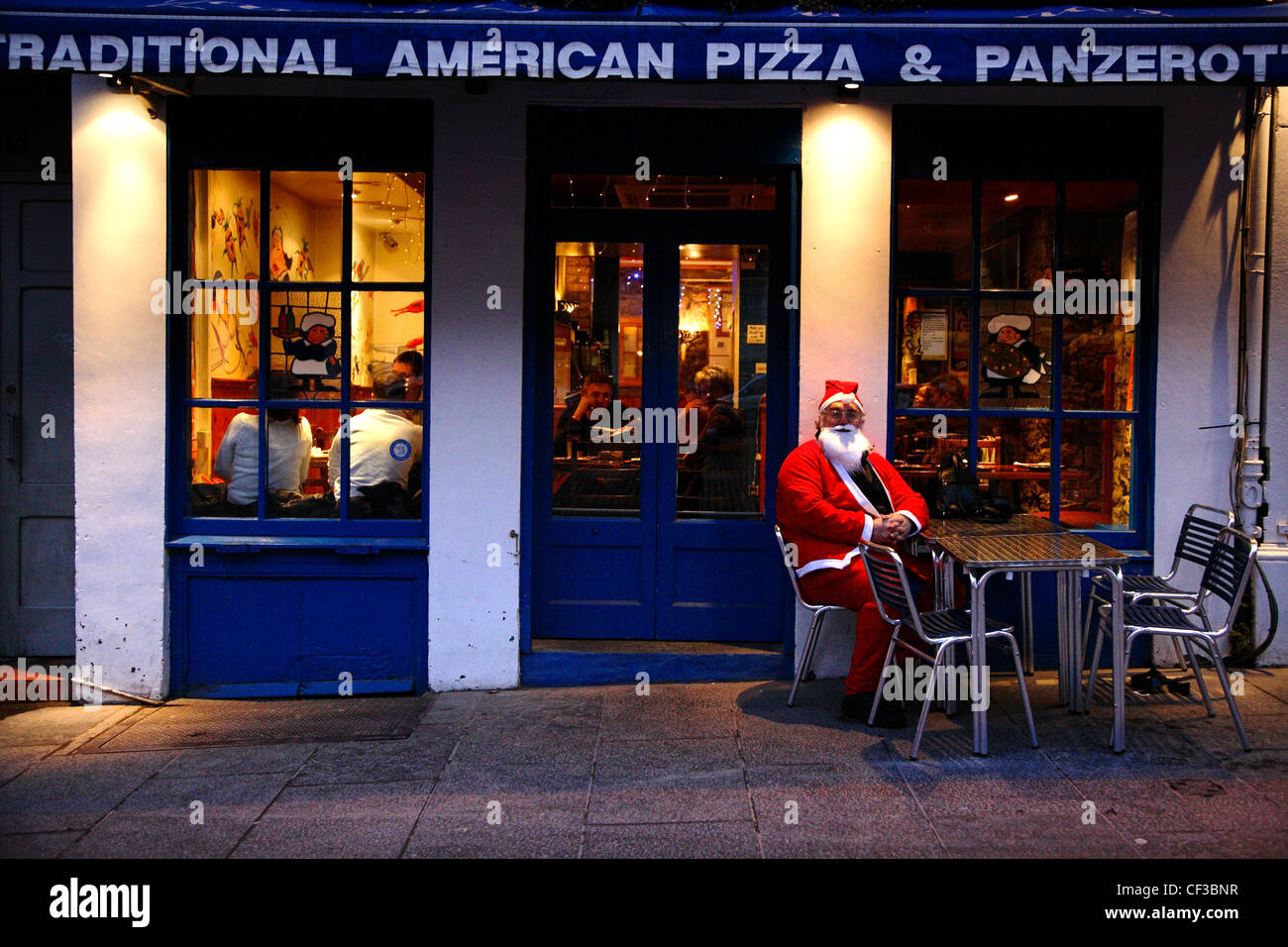 A man in costume sits outside a pizza restaurant during the Edinburgh Christmas Santa Stroll. - Stock Image