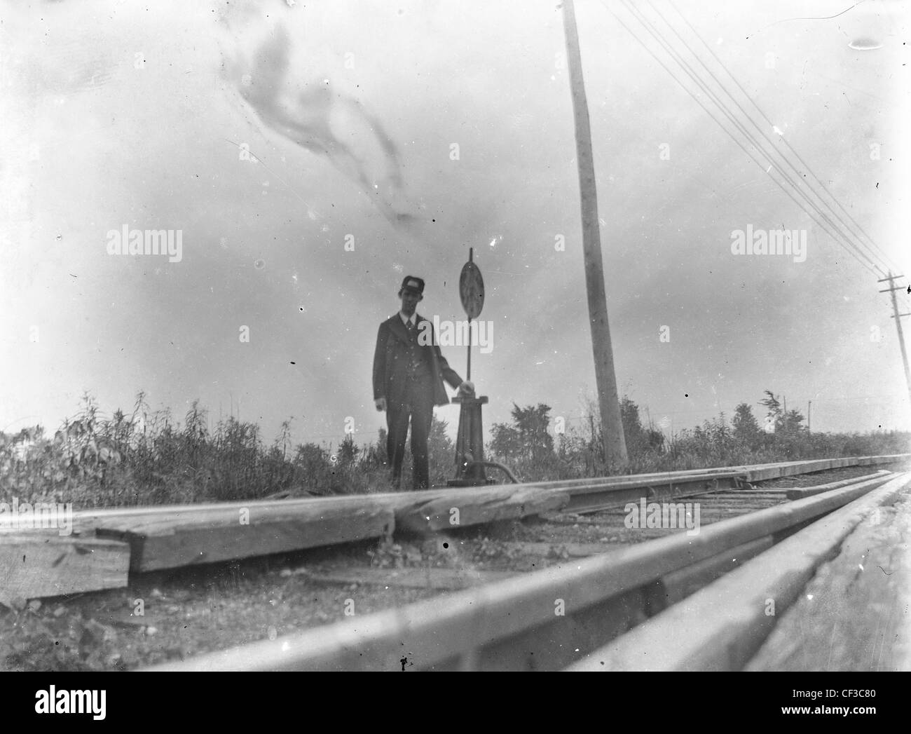 Railroad brake man worker standing next to tracks turn of the century 19th 1800s glass plate negative rails transportation - Stock Image