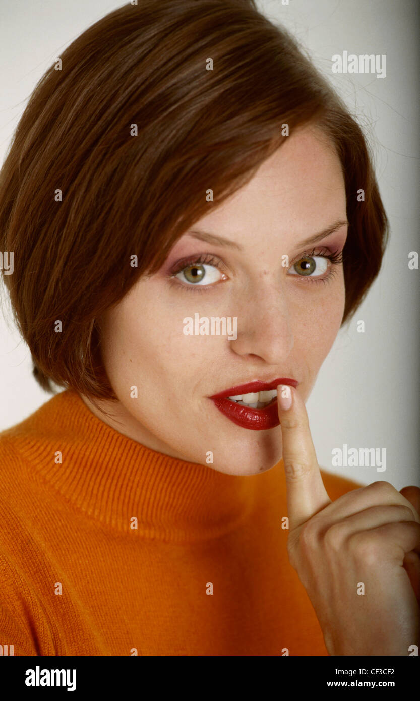 Female with short brunette hair, wearing an orange top, holding one finger to her mouth, looking at camera - Stock Image