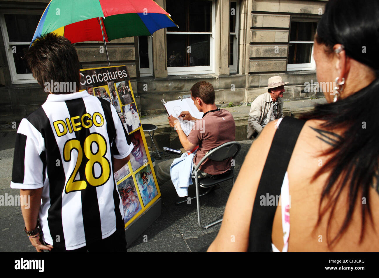 Cartoonists sketching caricatures on the Royal Mile during the Edinburgh festival fringe. - Stock Image