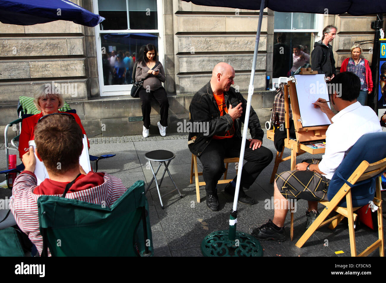 Cartoonists sketching caricatures of people on the Royal Mile. - Stock Image