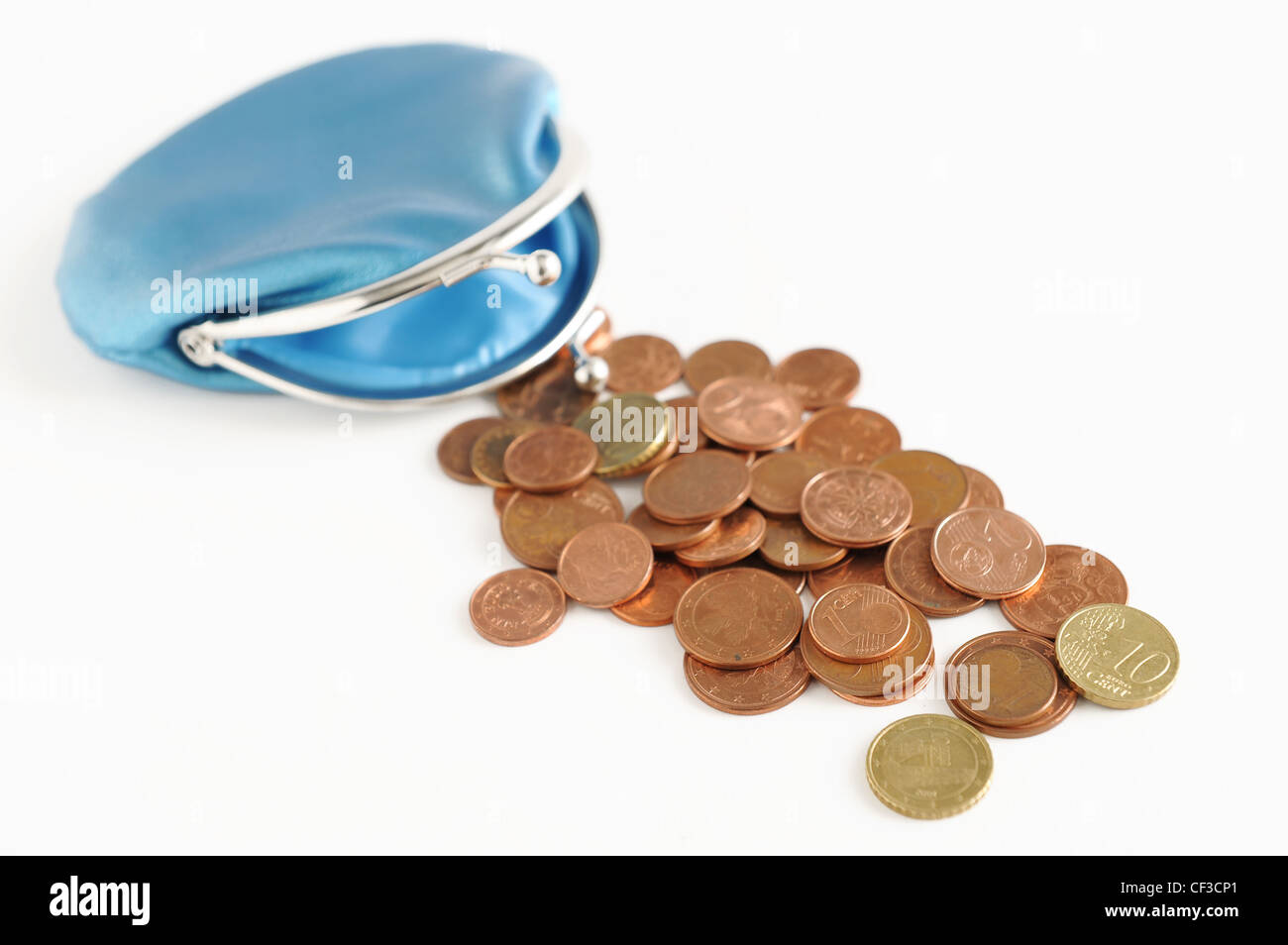 A still life image of Euro cent coins scattered on the white table with a blue coin purse in the corner Stock Photo