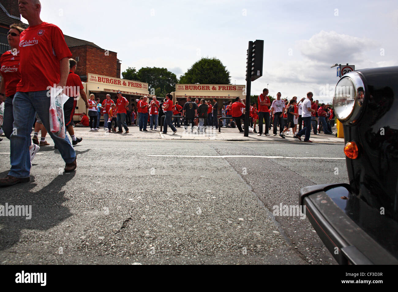 Liverpool football fans and burger vans on Anfield Road on a match day before kick off. - Stock Image