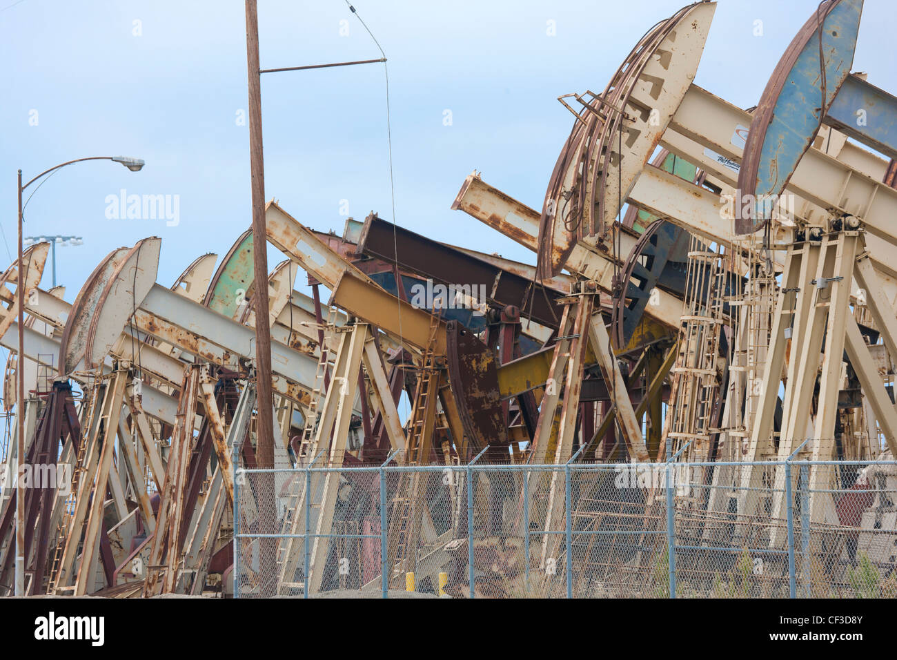 Long Beach California. Rows of rusty pumpjacks; pump jacks; nodding donkeys; oil well pump pumping units in the - Stock Image