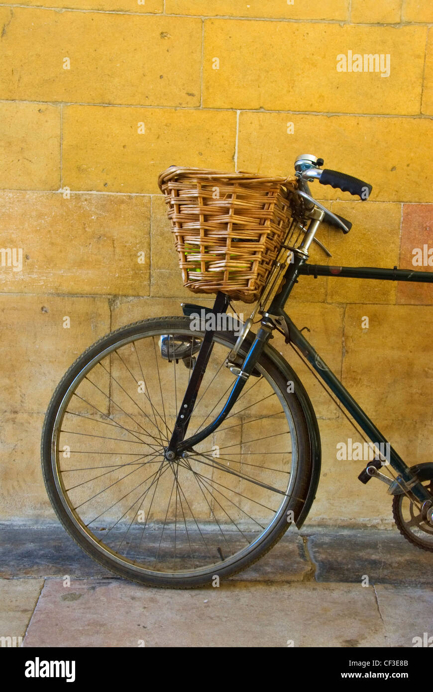 A bike leaning against a wall in Cambridge. Historically, Cambridge University students have not been permitted - Stock Image