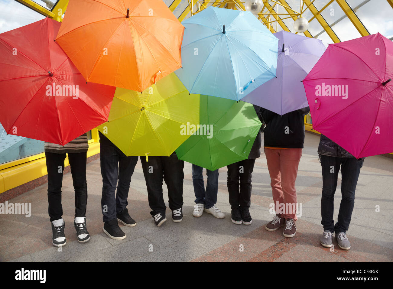 seven teens with opened umbrellas in pedestrian overpass - Stock Image