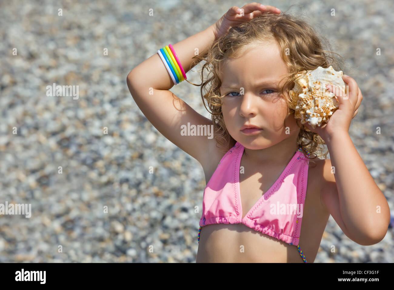 pretty little girl has leant seashell bowl to an ear on seacoast - Stock Image