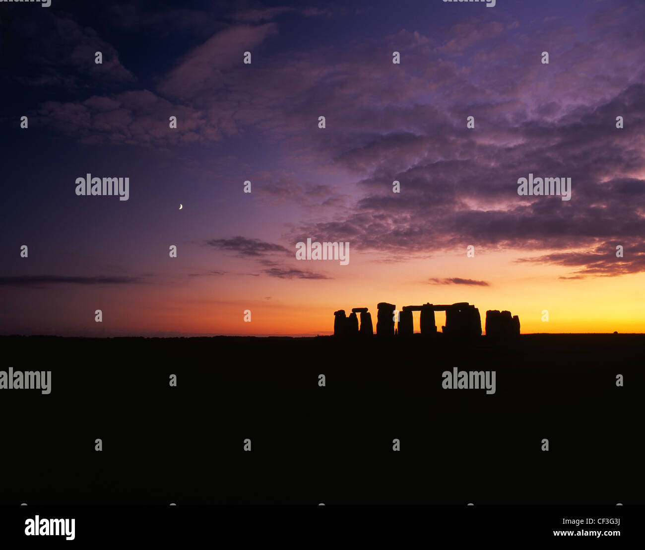 A wide landscape view of the Stonehenge trilithons silhouetted after sunset and moonrise. Stock Photo
