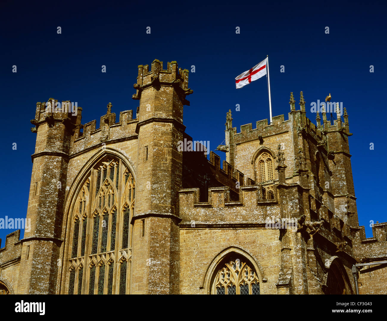 Flag of St George - red cross on a white background - flying from the tower of St Bartholomew's late Medieval - Stock Image