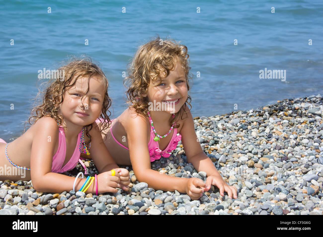 two pretty little girls lying on stony beach near sea - Stock Image