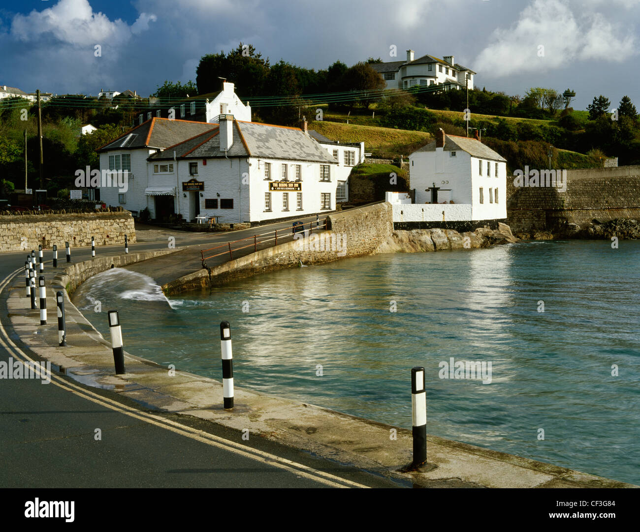 Early morning sunshine illuminates the Rising Sun Inn and Rock Cottage in Portmellon cove between Chapel Point and - Stock Image