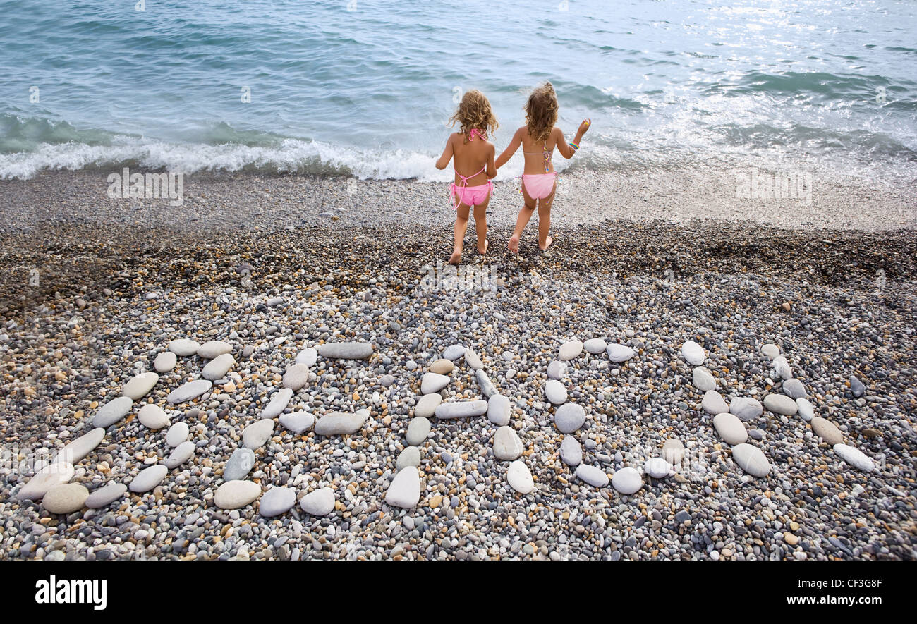 Inscription from stones BEACH at stony coast, two pretty little girls on seacoast - Stock Image