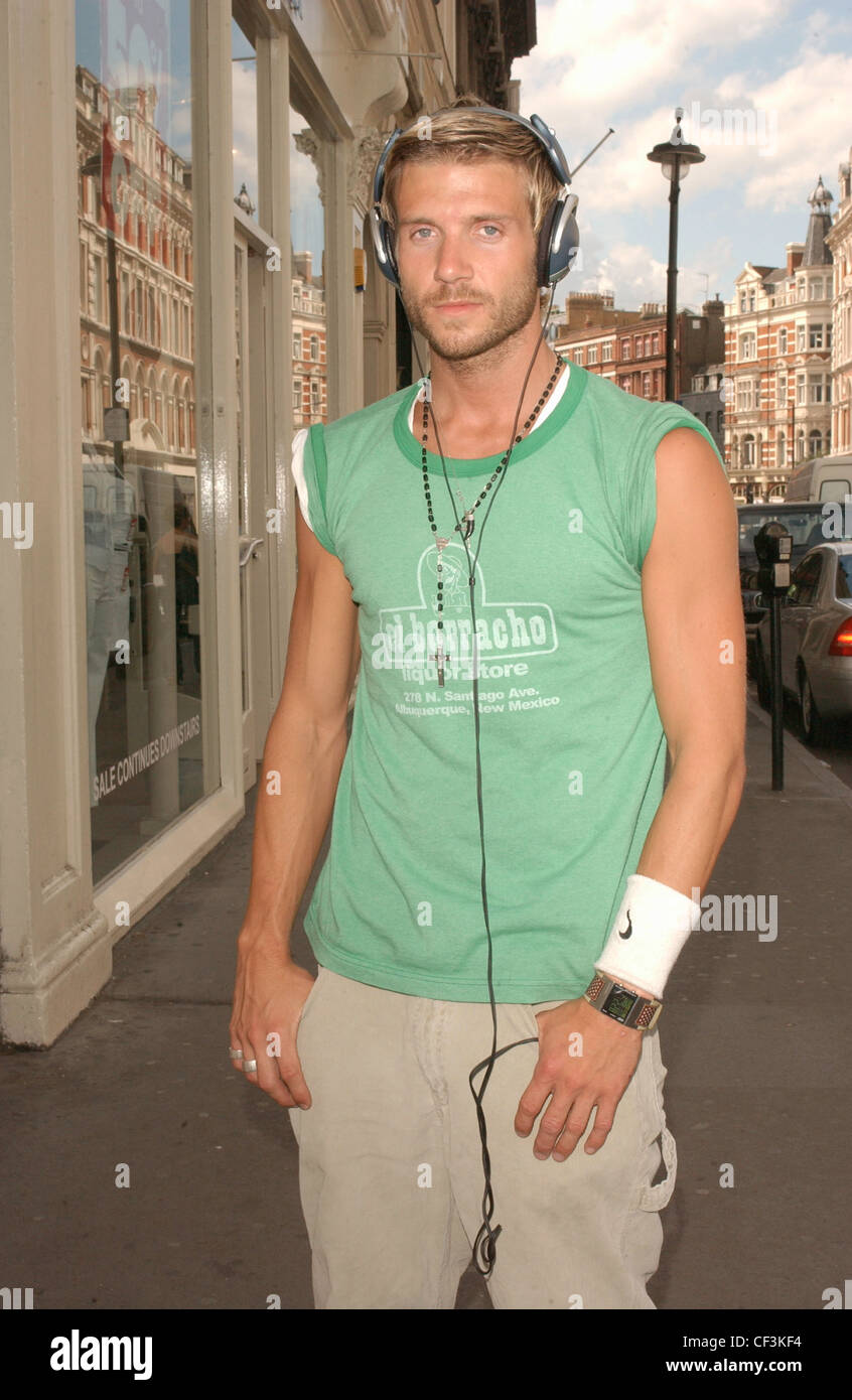 London Street Fashion Male blond hair and closely cropped beard wearing green t shirt sleeves rolled up beige trousers - Stock Image