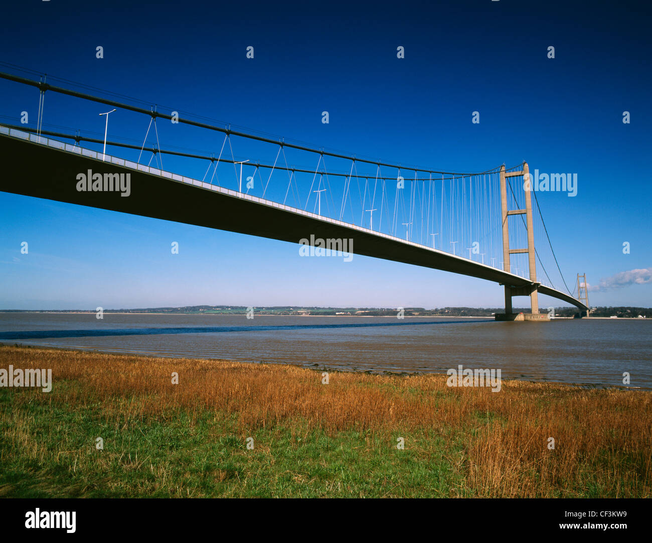 The Humber Bridge from the shore at Barton-upon-Humber crossing the Humber estuary to Hessle in East Yorkshire. - Stock Image