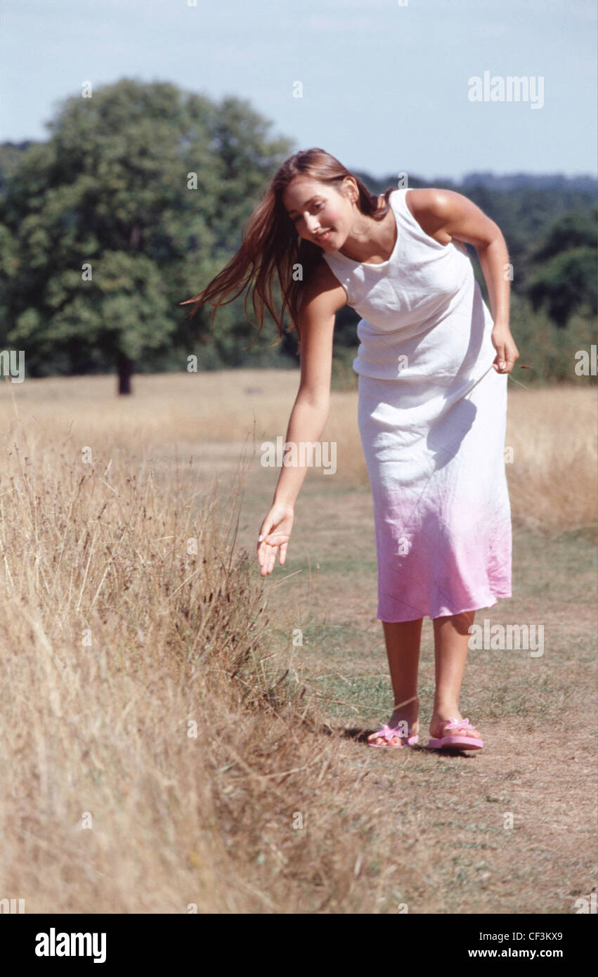 55844e74788f Female long brunette hair wearing white dress pink at bottom and pink flip  flops