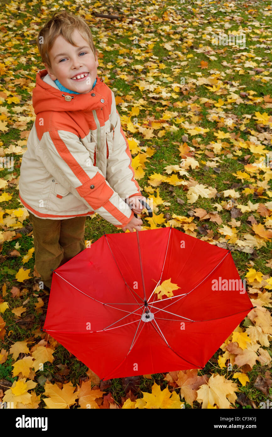 Portrait of boy in autumn park. Holds in lowered hand red umbrella. Top view. - Stock Image