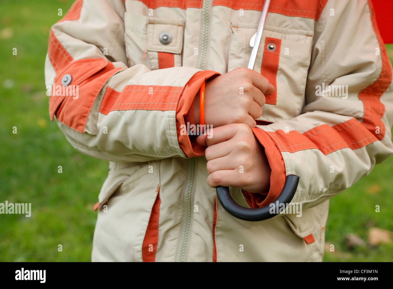 Hands of boy in jacket hold umbrella handle. Сlose up. Horizontal format. - Stock Image