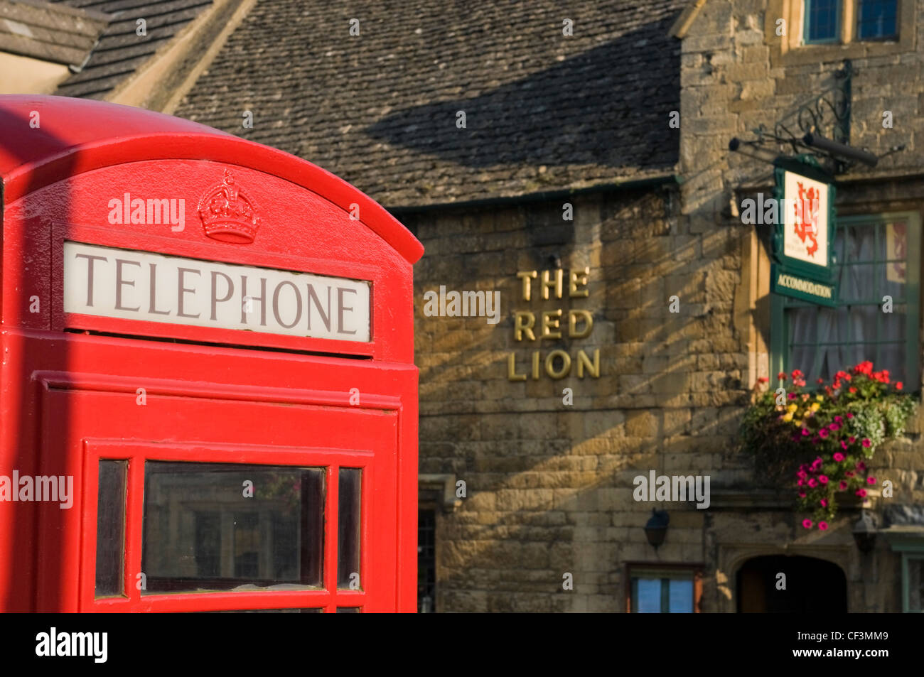 A traditional red telephone box outside the Red Lion pub in Chipping Camden. - Stock Image