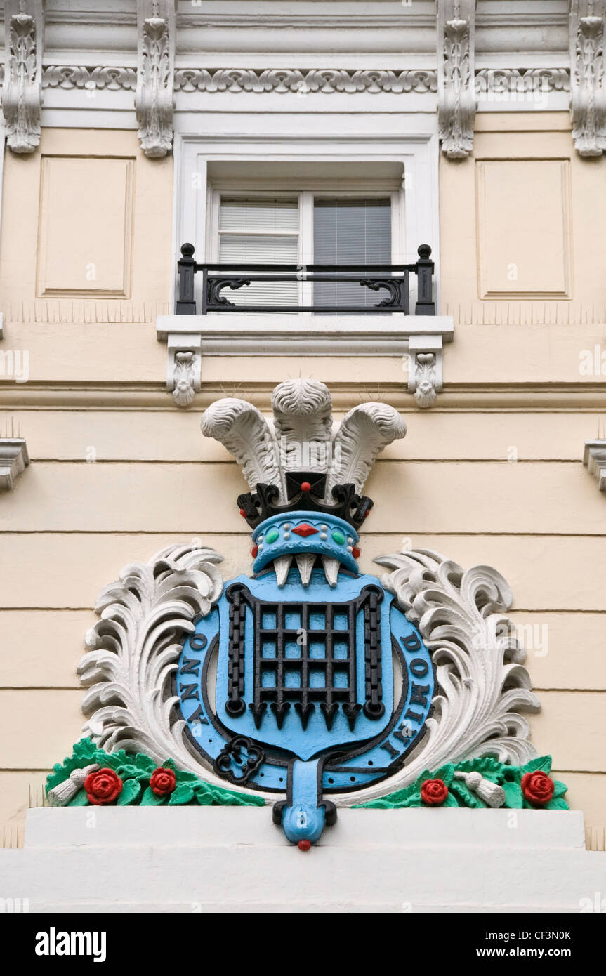 A cartouche of arms, with a wreathed portcullis surmounted by the Prince of Wales's Feathers above Moss Bros - Stock Image