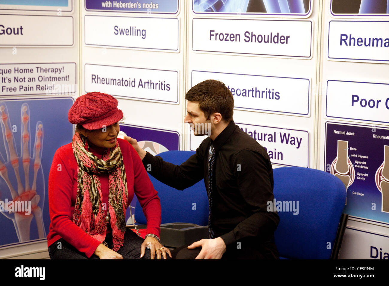 A female patient consulting a male doctor about arthritis of the shoulder, the back Pain show, London, UK - Stock Image
