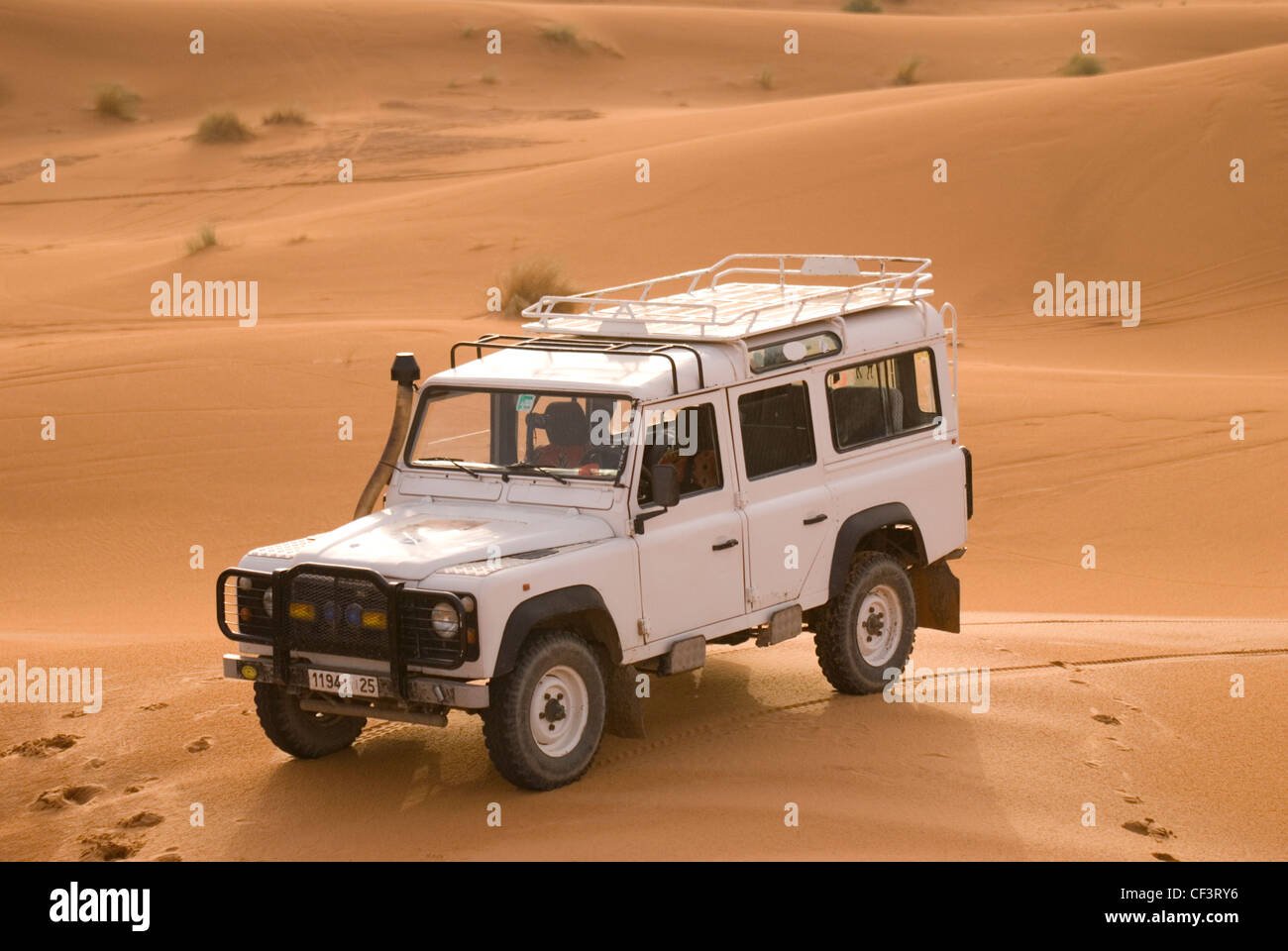 An off road 4x4 vehicle stands in the dunes of the Erg Chebi desert near Merzouga. - Stock Image