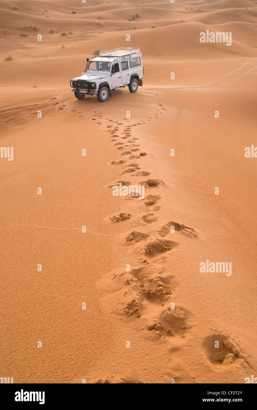 Foot prints in the sand lead to an off road 4x4 vehicle in the Erg Chebi desert. - Stock Image