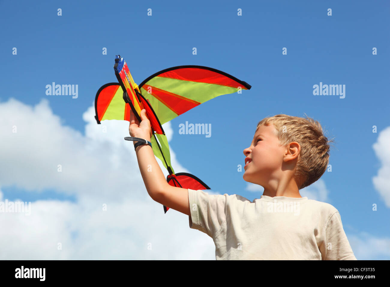 boy plays kite against sky - Stock Image