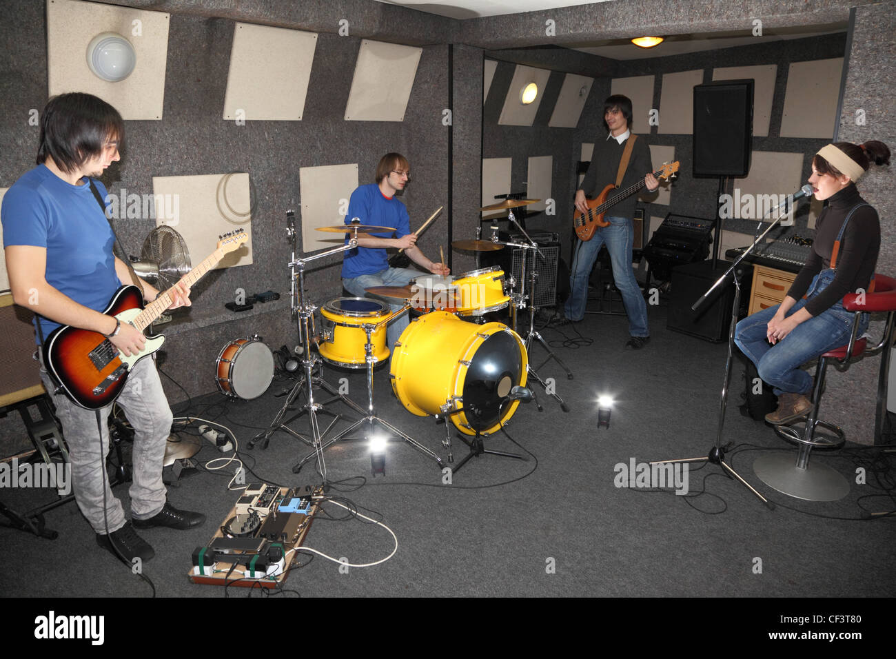 a rock band. vocalist girl, two musicians with electro guitars and one drummer working in studio. flashes in center - Stock Image