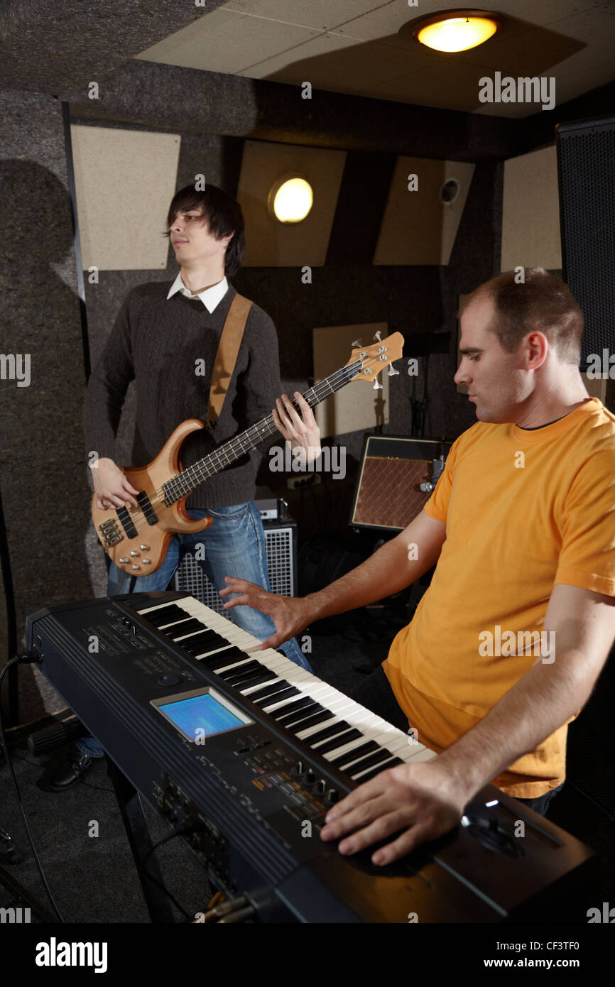 guitar player and keyboard player is working in studio. focus on distant part of synthesizer - Stock Image