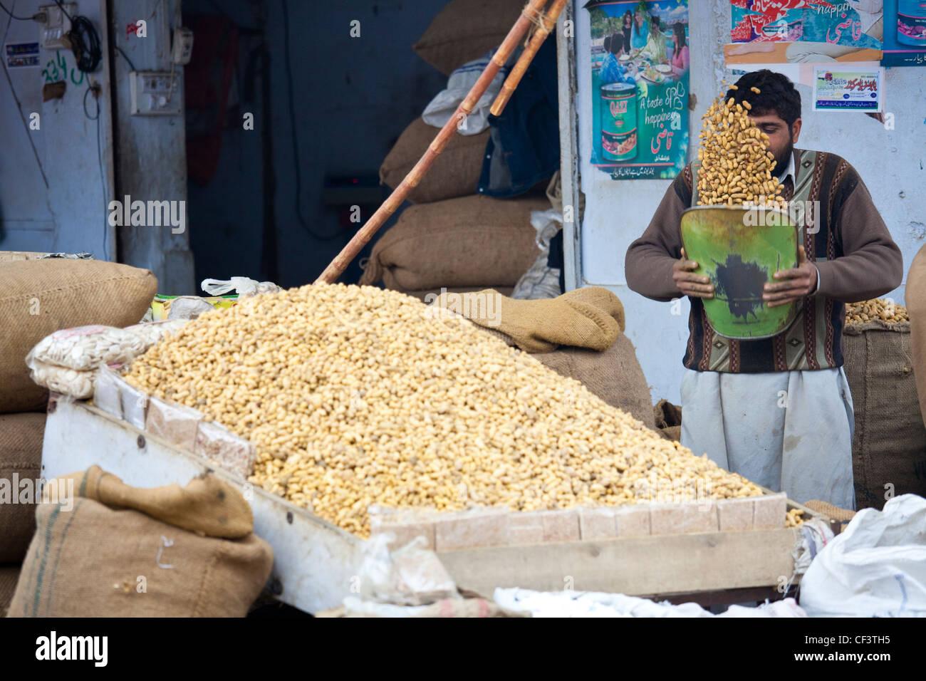 Nut vendor removing loose shells from peanuts, Islamabad, Pakistan - Stock Image