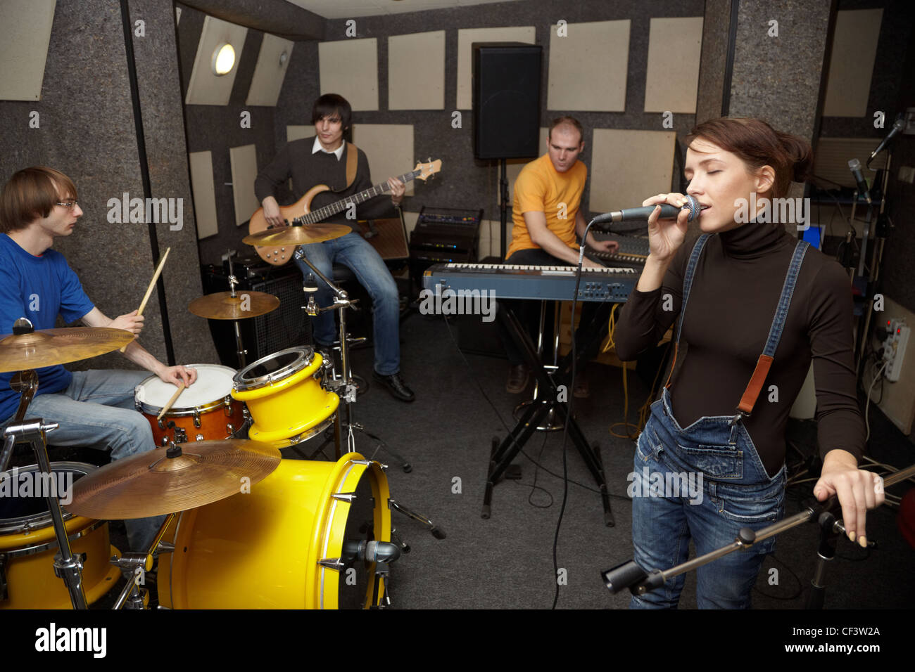 a rock band working in studio. vocalist girl is singing. focus on clothers of vocalist girl - Stock Image