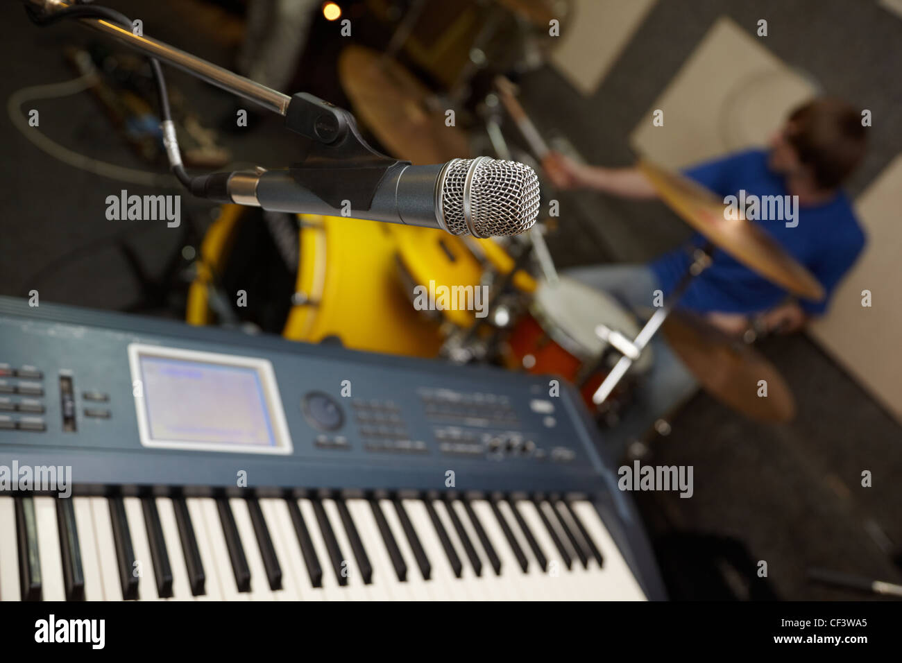 microphone near synthesizer. drummer in out of focus - Stock Image