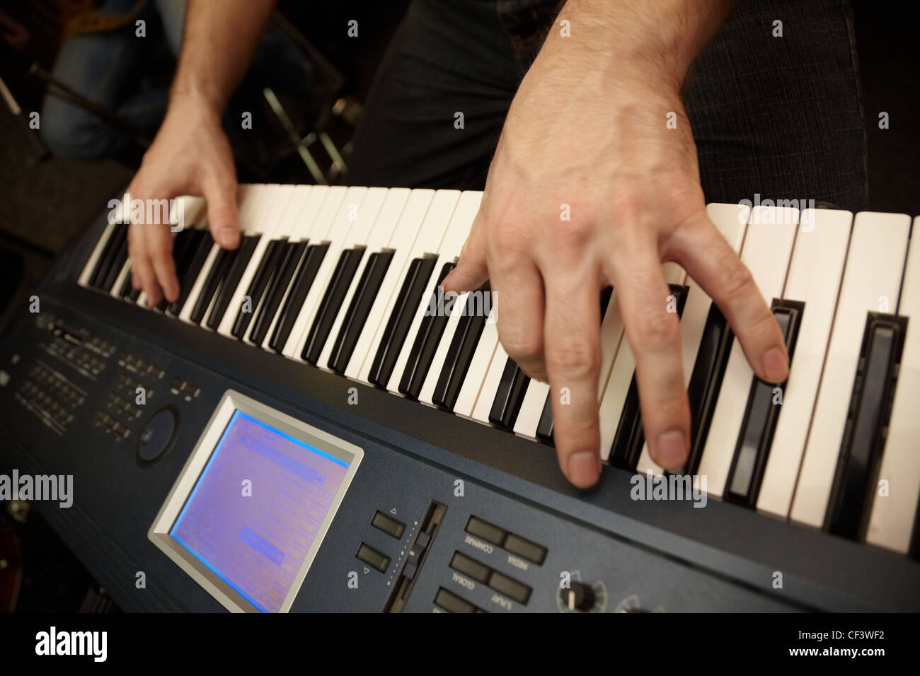 hands of keyboard player on keys of synthesizer. focus on big finger of left hand - Stock Image