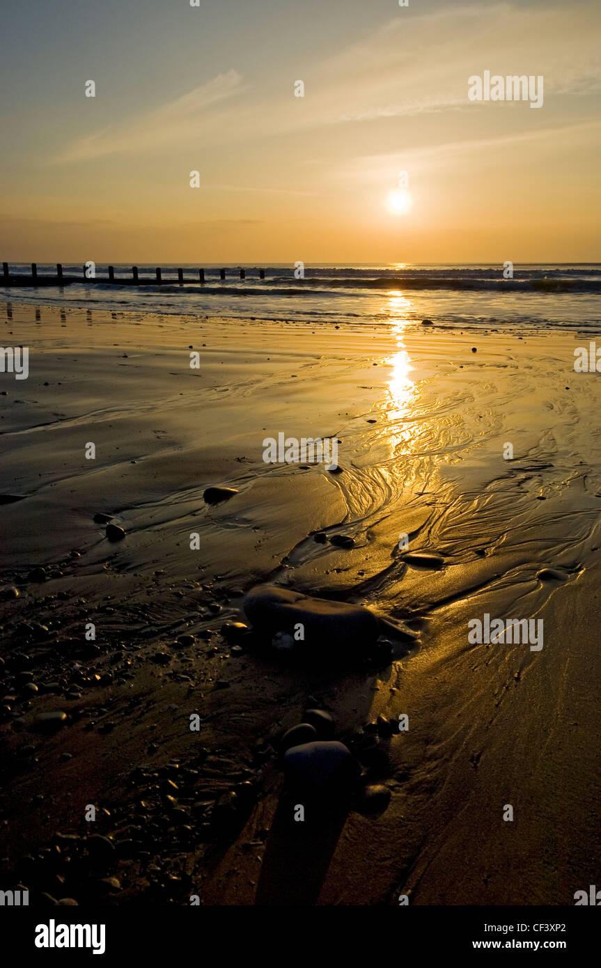 Tide rolling onto the beach past a breakwater at dusk. - Stock Image