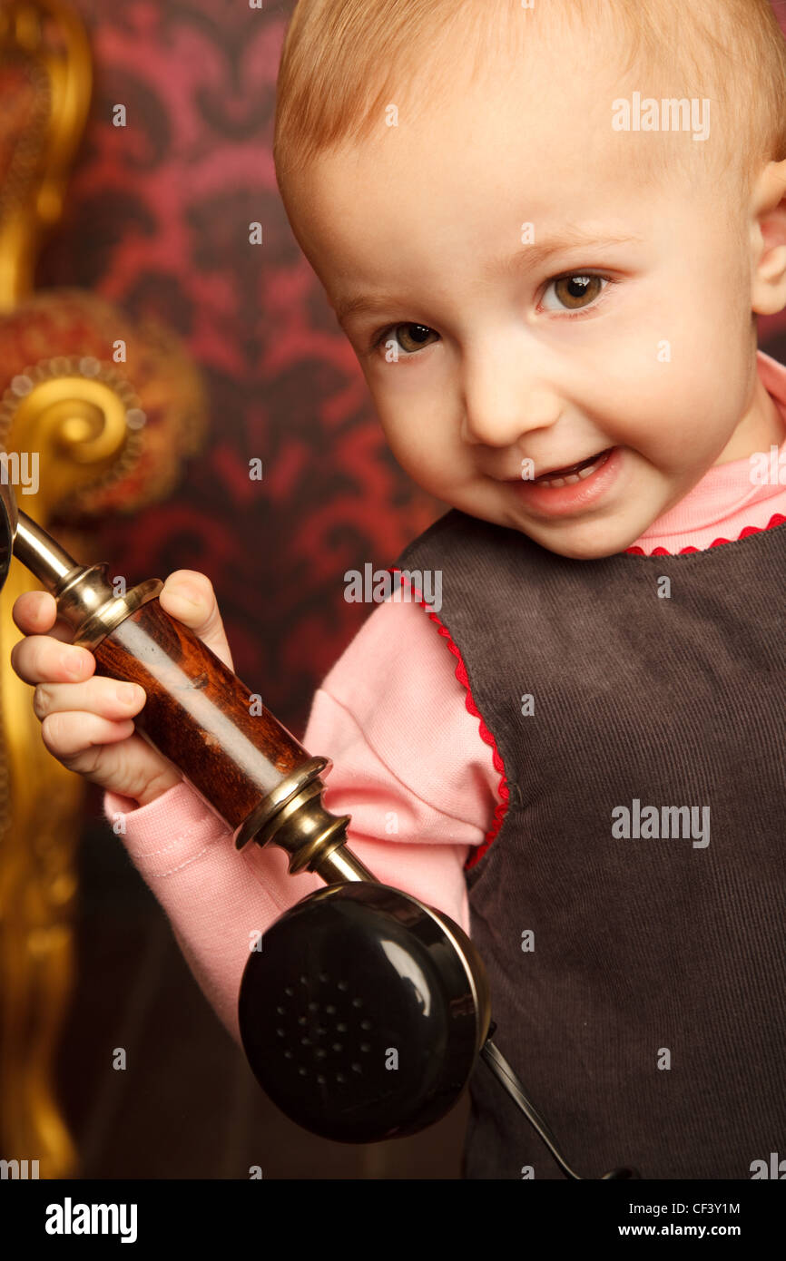 Portrait of little girl holds up retro phone. Interior in retro style. Сlose up. - Stock Image