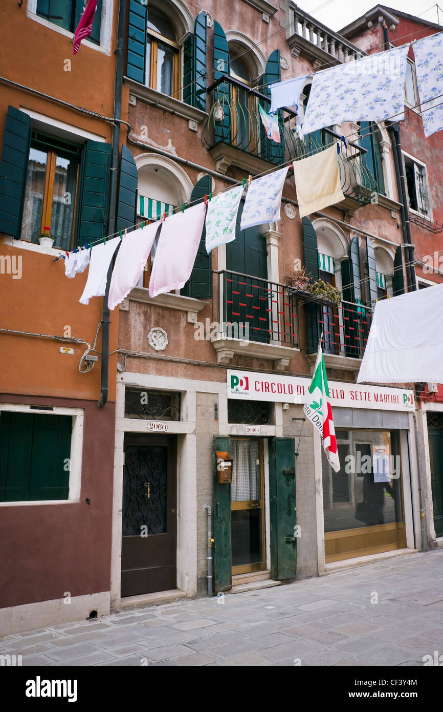 Laundry drying on clothesline between two buildings in Castello district - Venice, Venezia, Italy, Europe - Stock Image