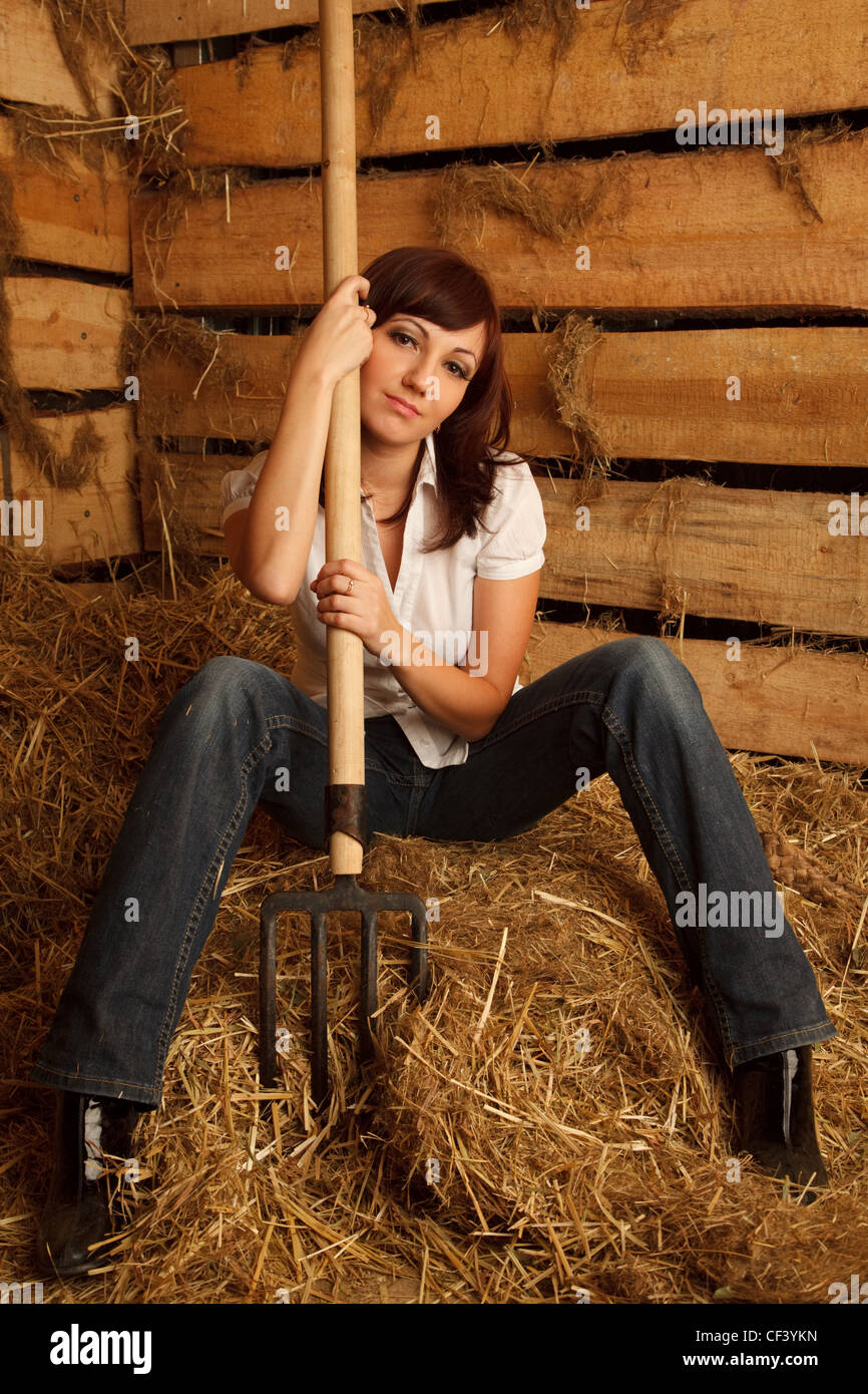 Portrait of girl in white shirt and blue jeans on pile of straw in hayloft. Vertical format. - Stock Image